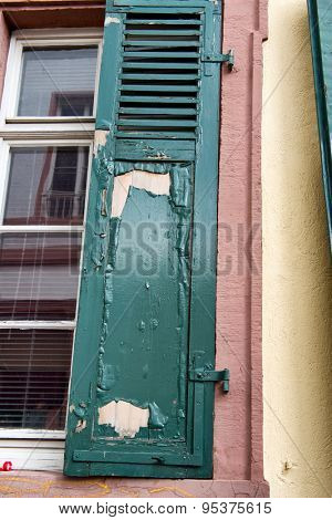 Low Angle Close Up View of Neglected Green Window Shutter with Chipped and Peeling Paint