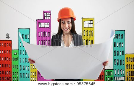 excited woman in orange hardhat with blueprint over grey wall with variegated drawing houses