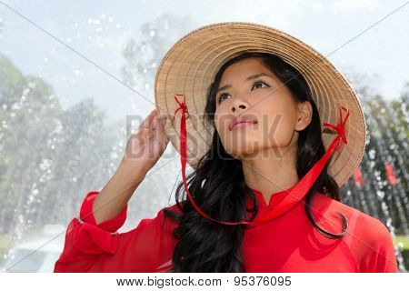 Vietnamese woman in a traditional red outfit and conical hat standing in front of a fountain