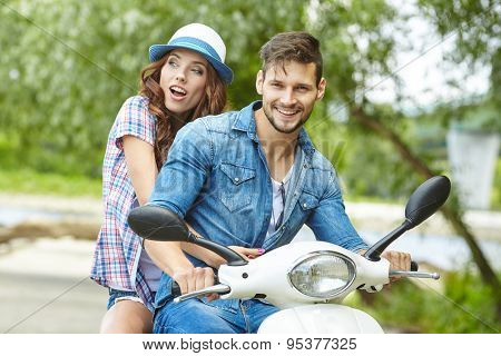 Riding with fun. Beautiful young couple riding scooter together while happy woman raising arms and smiling