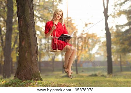 Joyful girl in a red dress reading a book seated on swing in a park