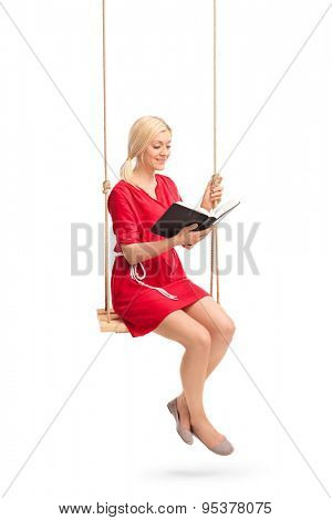 Vertical shot of a young woman in a red dress sitting on a swing and reading a book isolated on white background