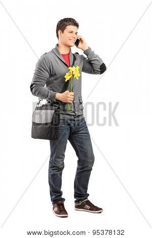 Full length portrait of a young man holding a few yellow tulips and talking on his cell phone isolated on white background