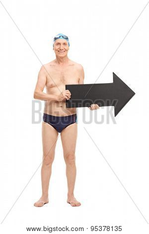 Full length portrait of a senior man in a black swim trunks holding a big black arrow pointing right and looking at the camera isolated on white background