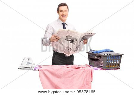 Cheerful guy holding a newspaper behind an ironing board.The newspaper is custom made, the text is Latin and the pictures are my copyright. You can find them and the necessary Model Releases attached.