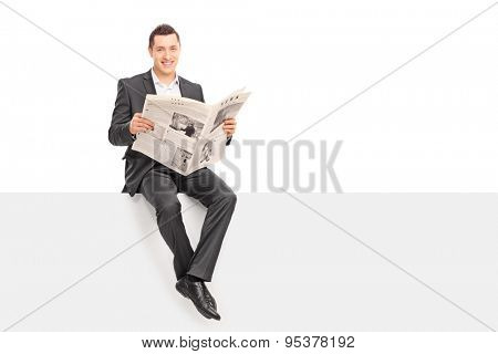 Young businessman holding newspaper seated on signboard. The newspaper is custom made, the text is Latin and the pictures are my copyright.
