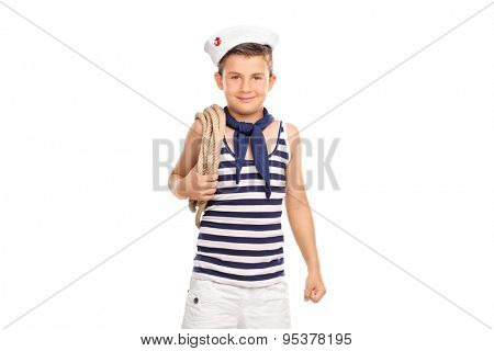 Cute little boy in a sailor outfit carrying a rope around his shoulder and looking at the camera isolated on white background
