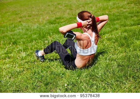 Sporty girl doing situps in park