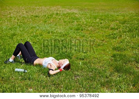 Young woman in activewear relaxing on green lawn