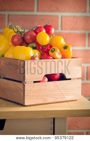 peppers and tomatoes in wooden box on kitchen table