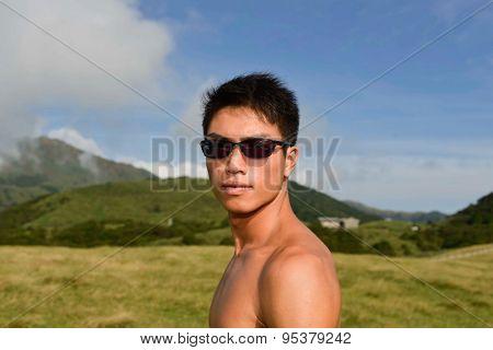 sport model. -Yong muscular man in sunglasses on mountain grass