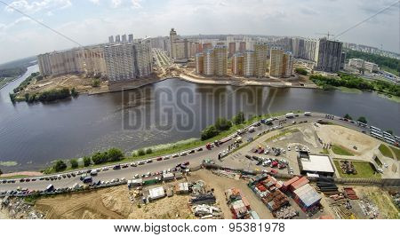 RUSSIA, KRASNOGORSK - JUN 6 2014: Cityscape with playground for off-road test drives of Jeep company and tall dwelling houses on shore of Moscow river. Aerial view. Photo with noise from action camera