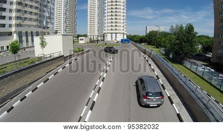 RUSSIA, MOSCOW - JUN 1, 2014: Aerial view of two cars ride by yard with playground near residential complex on Elk Island at sunny day. Photo with noise from action camera