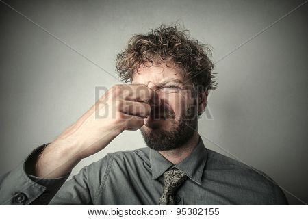 Disgusted man smelling a bad smell