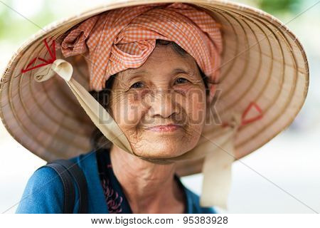 HO CHI MINH CITY ( SAIGON ), VIETNAM, FEBRUARY 22, 2015 : Portrait of a cute elderly lady wearing a traditional conical hat in Ho Chi Minh city, Vietnam