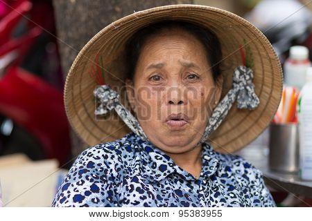 SAIGON, VIETNAM, FEBRUARY 26, 2015 : A funny senior woman is making a grimace in the streets of Saigon (Ho Chi Minh), Vietnam