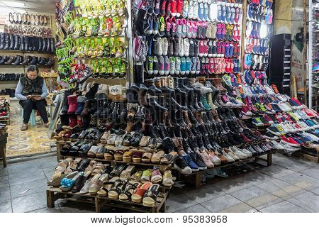 HANOI, VIETNAM, DECEMBER 15, 2014 : A woman is sitting in her shop specialized in the selling of shoes in Hanoi, Vietnam