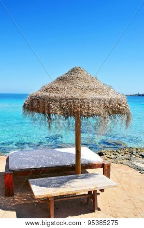 detail of a relaxing area in a beach in Ibiza, Spain, with a comfortable sun lounger and a rustic umbrella made of natural fibers
