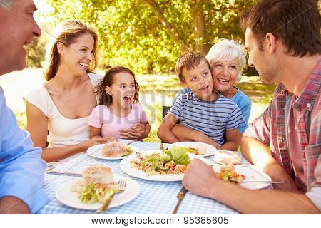 Multi-generation family eating together outdoors