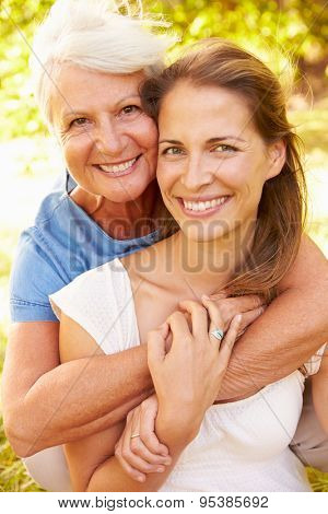 Senior woman sitting outdoors with her adult daughter