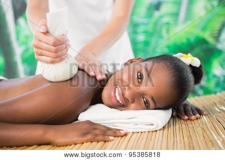 Side view of a pretty woman enjoying a herbal compress massage at the health spa