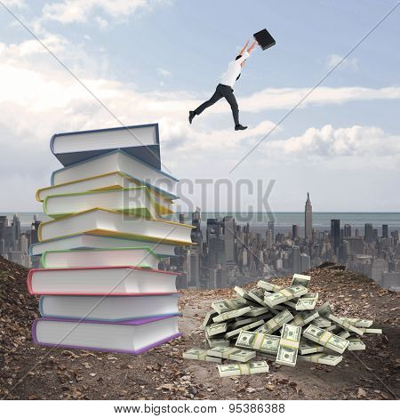Businessman leaping with his briefcase against stack of books