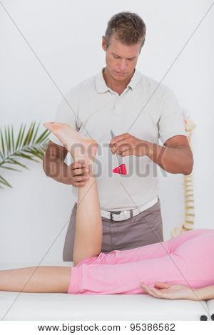 Physiotherapist using reflex hammer in medical office