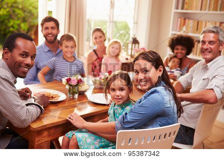 Family and friends sitting at a dining table, looking at camera