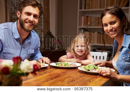 Family eating dinner at a dining table, looking at camera