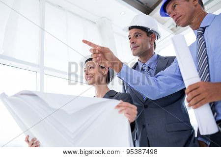 Businessman explaining a blueprint to his colleagues in the office
