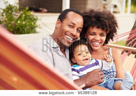 Happy couple�¿with young child sitting in a hammock