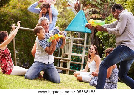 Adults and kids having fun with water pistols in a garden