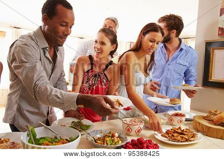 Friends serving themselves food and talking at dinner party