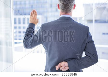 Businessman making a oath while crossing fingers behind his back