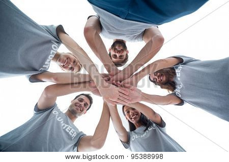 Low angle of happy volunteers putting theirs hands together
