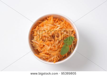 bowl of grated carrot on white background