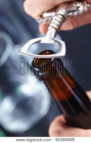 A hand opening a bottle of beer