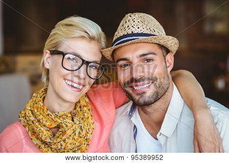 Portrait of cute couple on a date looking at the camera at the cafe