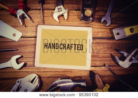 The word hand crafted and tablet pc against blueprint