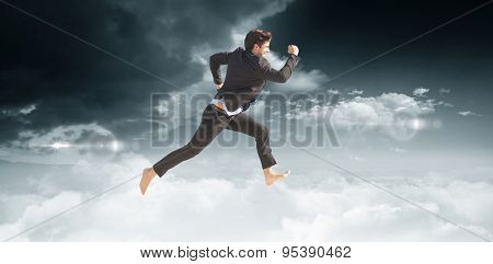 Businessman leaping against bright blue sky with clouds