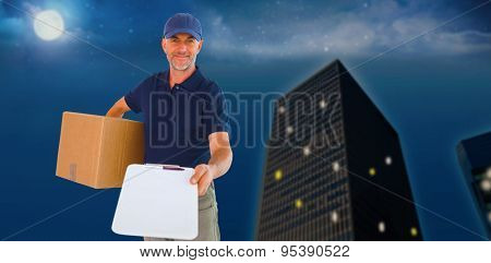 Happy delivery man holding cardboard box and clipboard against city at night