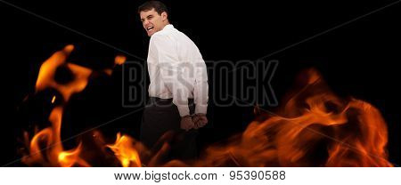 Rear view of young businessman wearing handcuffs against black
