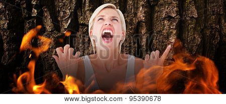 Upset woman screaming with hands up against brown rough bark