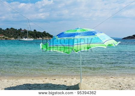 Umbrella on the beach and yacht in a background