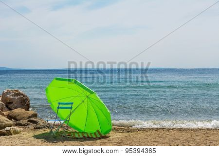 Chair in the shadow of an umbrella on the beach