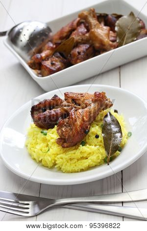 chicken and pork adobo over yellow rice, filipino food