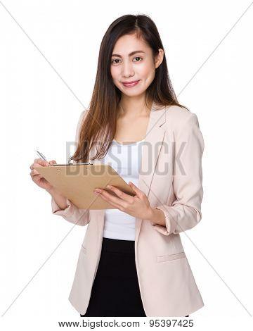 Businesswoman write on clipboard