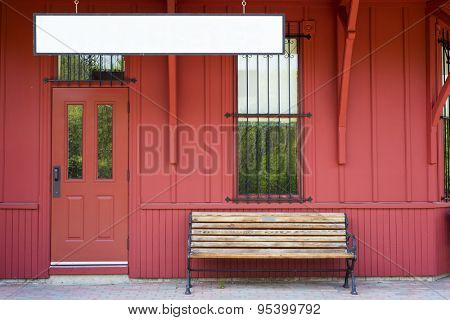 Empty bench by blank sign against red wooden walls