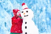 Funny little toddler girl in a red knitted Nordic hat and warm coat playing with a snow poster