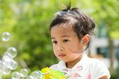 stock photo of blowers  - Little girl play with bubble blower - JPG